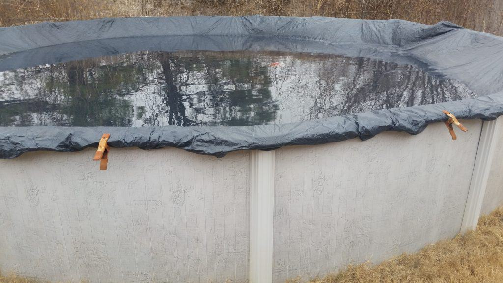 Above ground swimming pool with the winter cover over it.