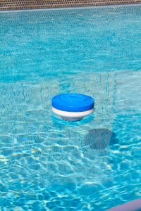 Floating chlorine dispenser floating along the water.