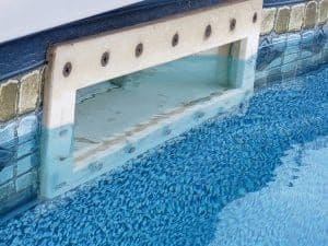 Pool skimmer at the surface water.