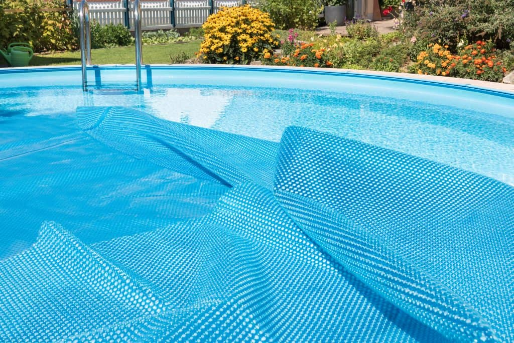 A pool with a cover partially covering the surface of the water.