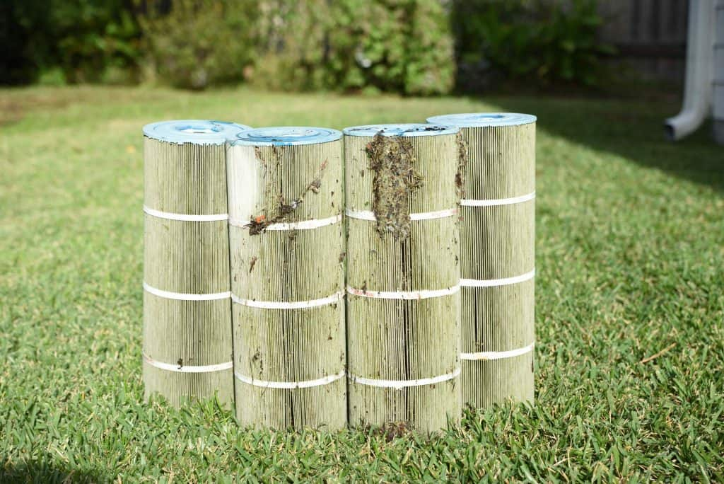 4 dirty cartridge filters on the grass.