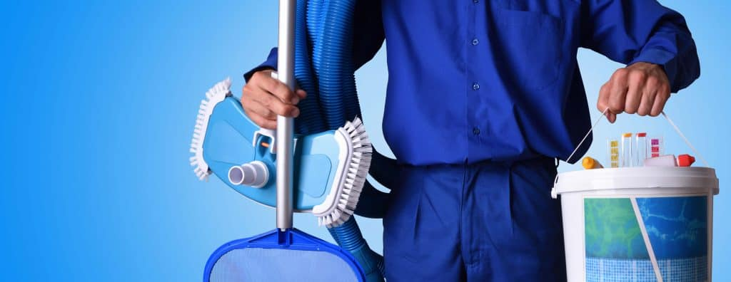 Person carrying a pool skimmer, vacuum head and pool chemicals.
