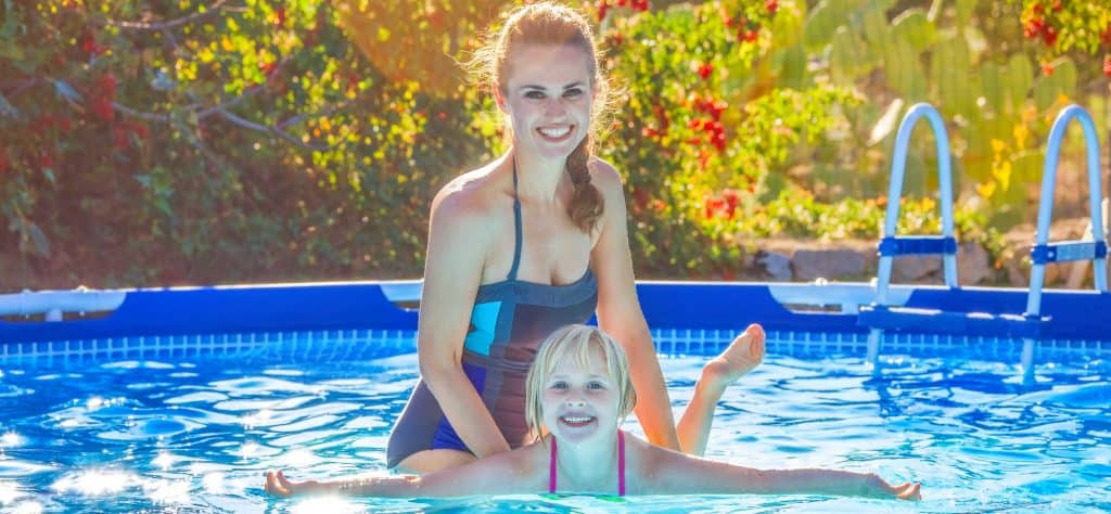 Lady and child swimming in an above ground pool.