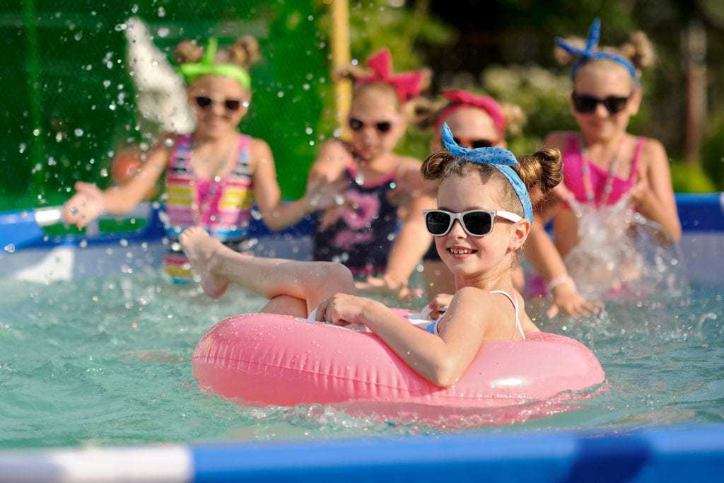 Group of young girls wearing sunglasses floating in inner tubes having some pool fun.