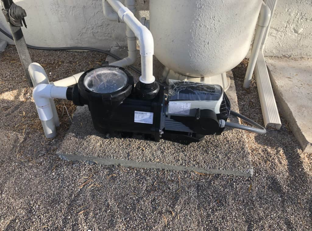 Swimming pool pump connected to the pools plumbing and sand filter.